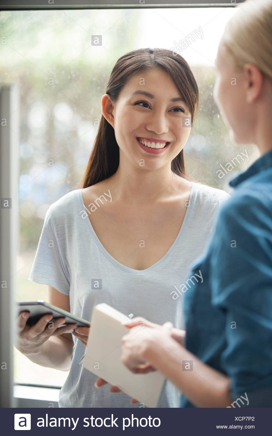 Woman chatting with friend, smiling - Stock Image