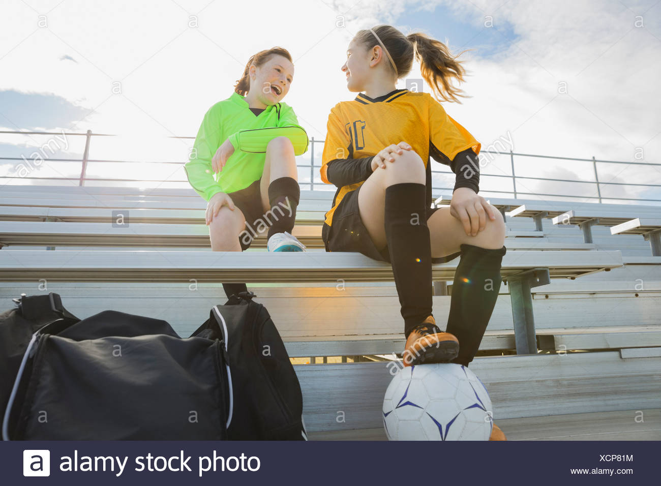 Girls in soccer uniforms sitting on bleachers Stock Photo