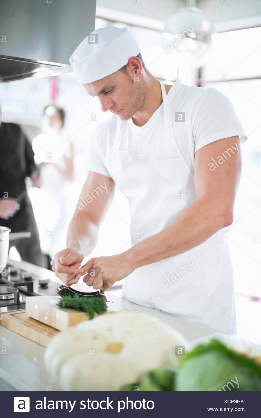 Male chef mixing using herb chopper in commercial kitchen - Stock Image