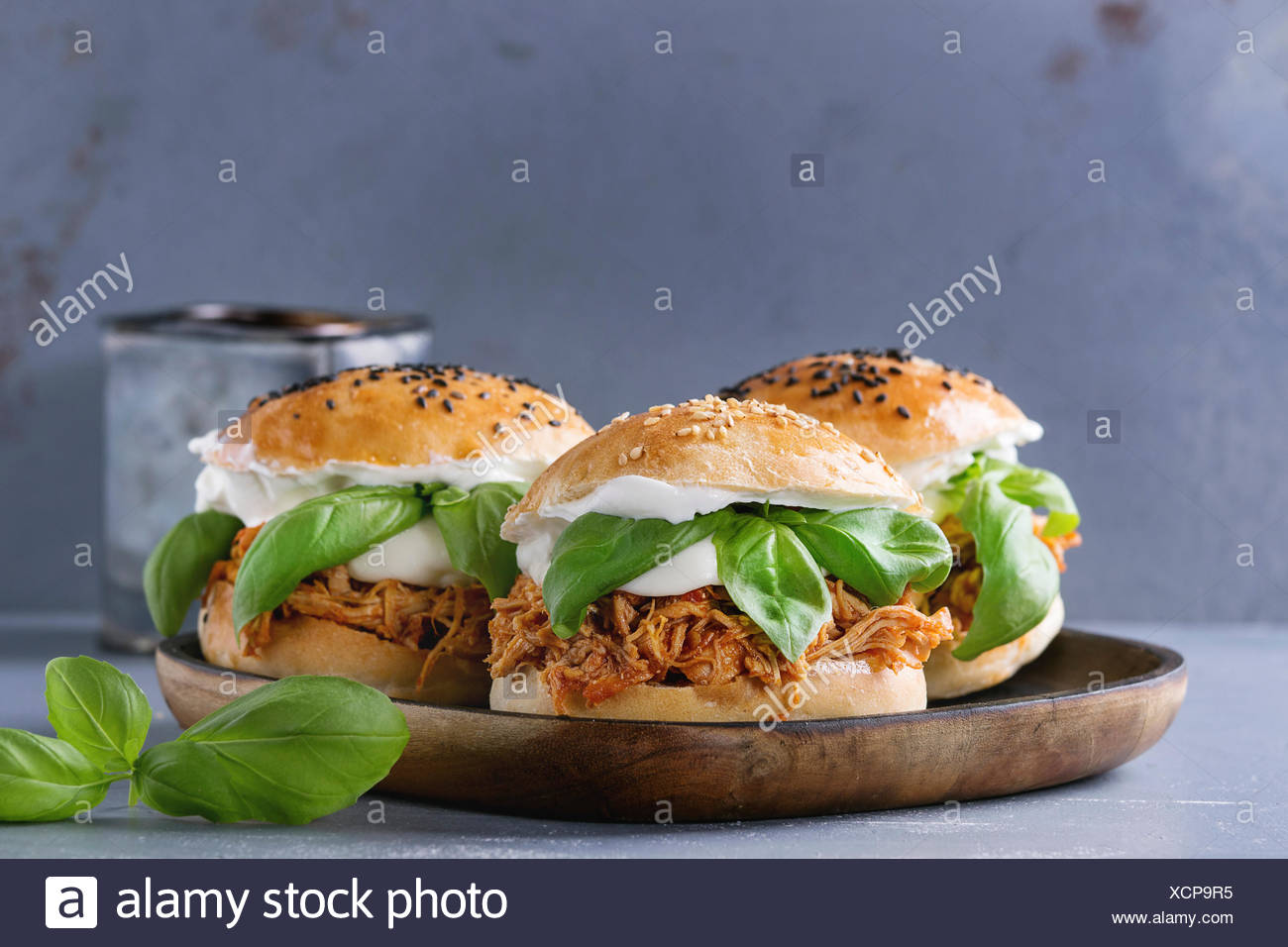 Homemade mini burgers with pulled chicken, basil, mozzarella cheese and yogurt sauce on wooden plate over gray texture background. Healthy fast food c - Stock Image