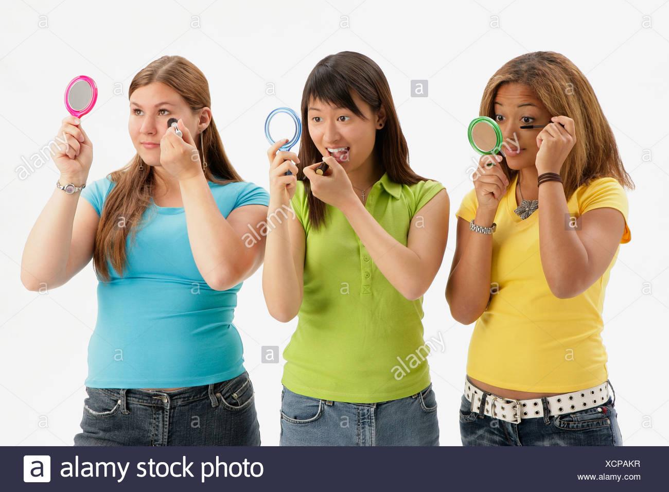 Three teens applying makeup - Stock Image