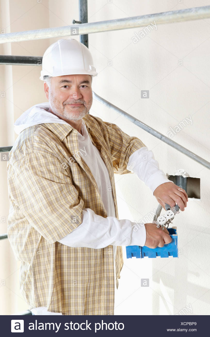 Portrait of a mature man holding construction equipment Stock Photo