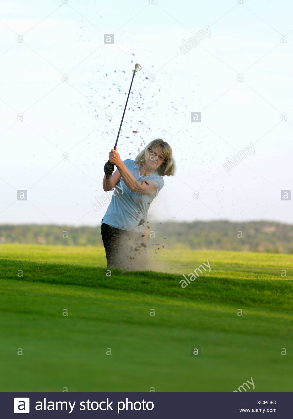 Woman in golf bunker - Stock Image