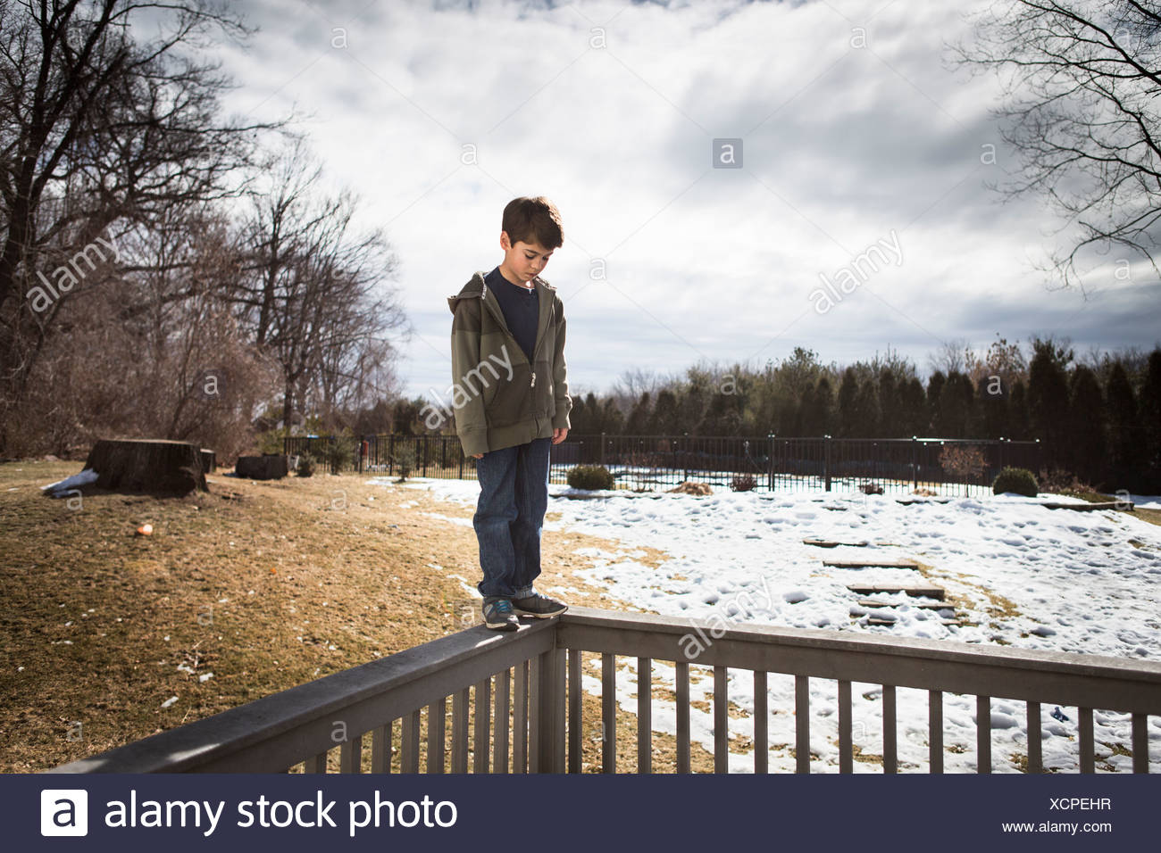 Boy balancing on top of fence in park - Stock Image