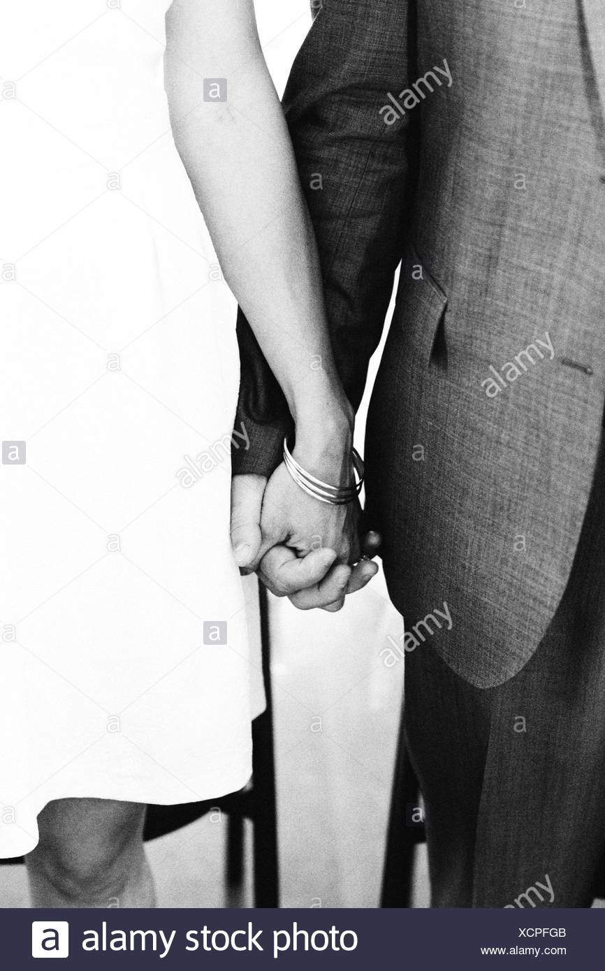 Midsection Of Couple Holding Hand Of Each Other - Stock Image