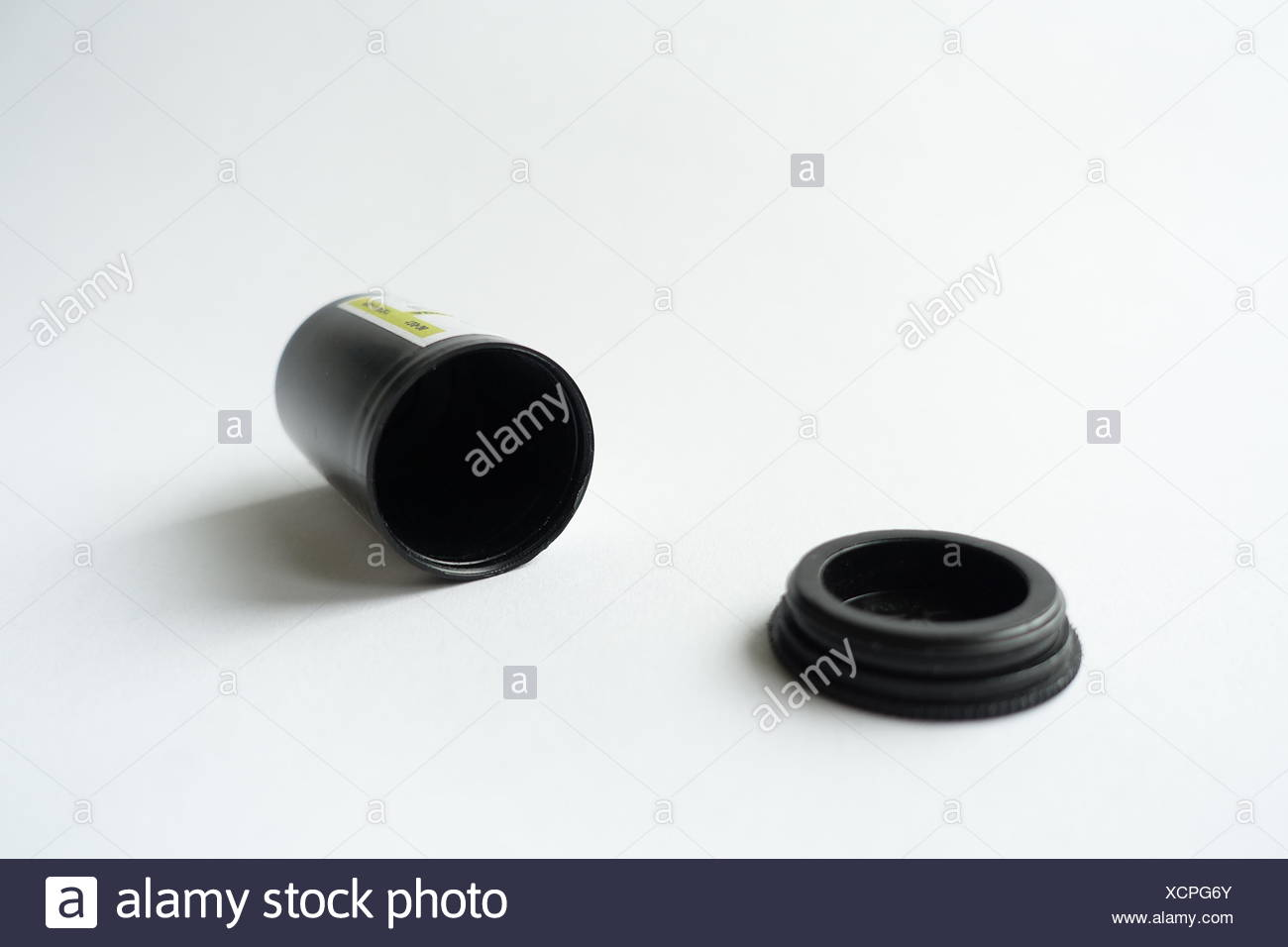 Close-Up Of Empty Film Canister On White Table - Stock Image