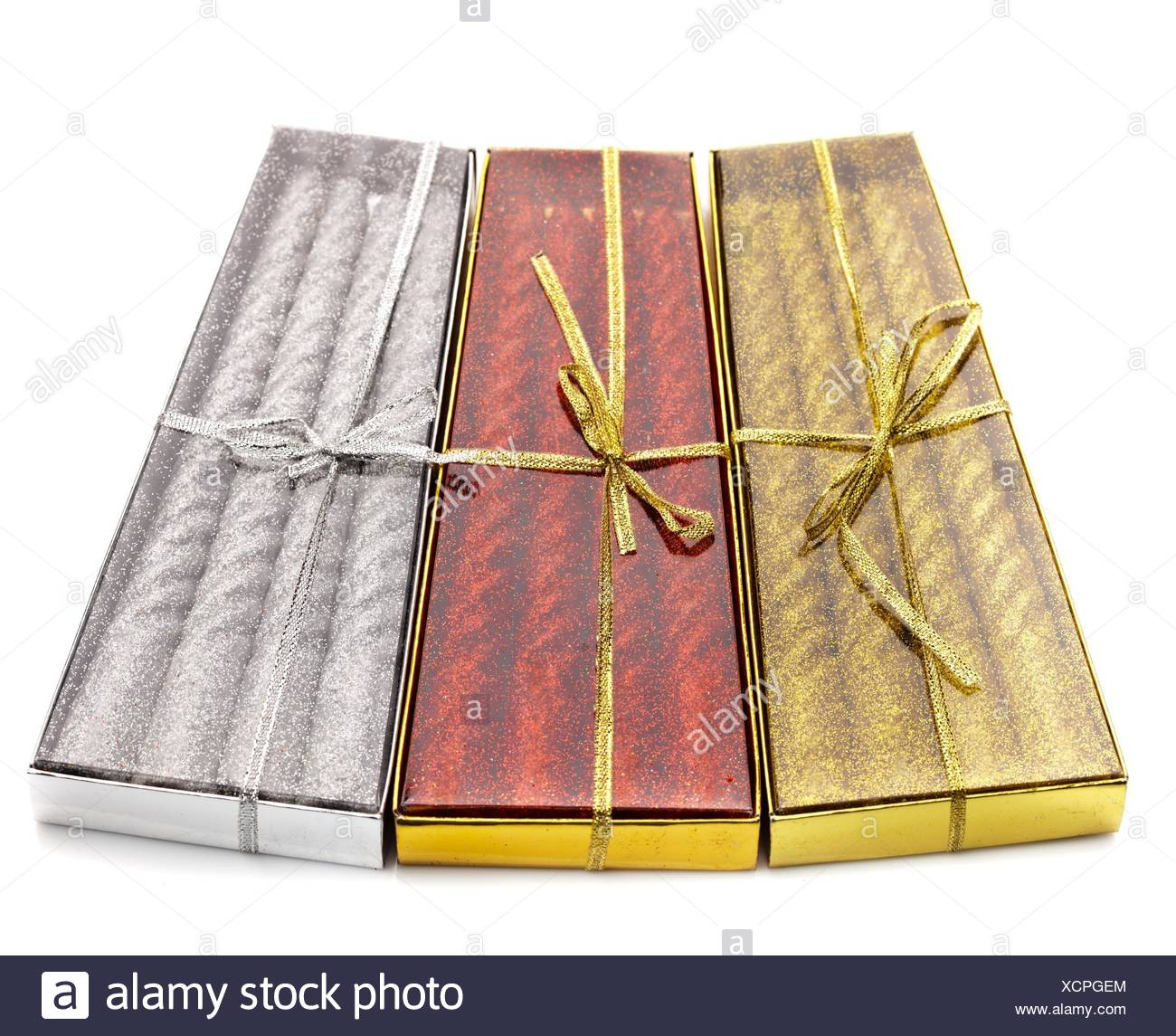 Three packs of Christmas candles red, silver and gold on white table. - Stock Image