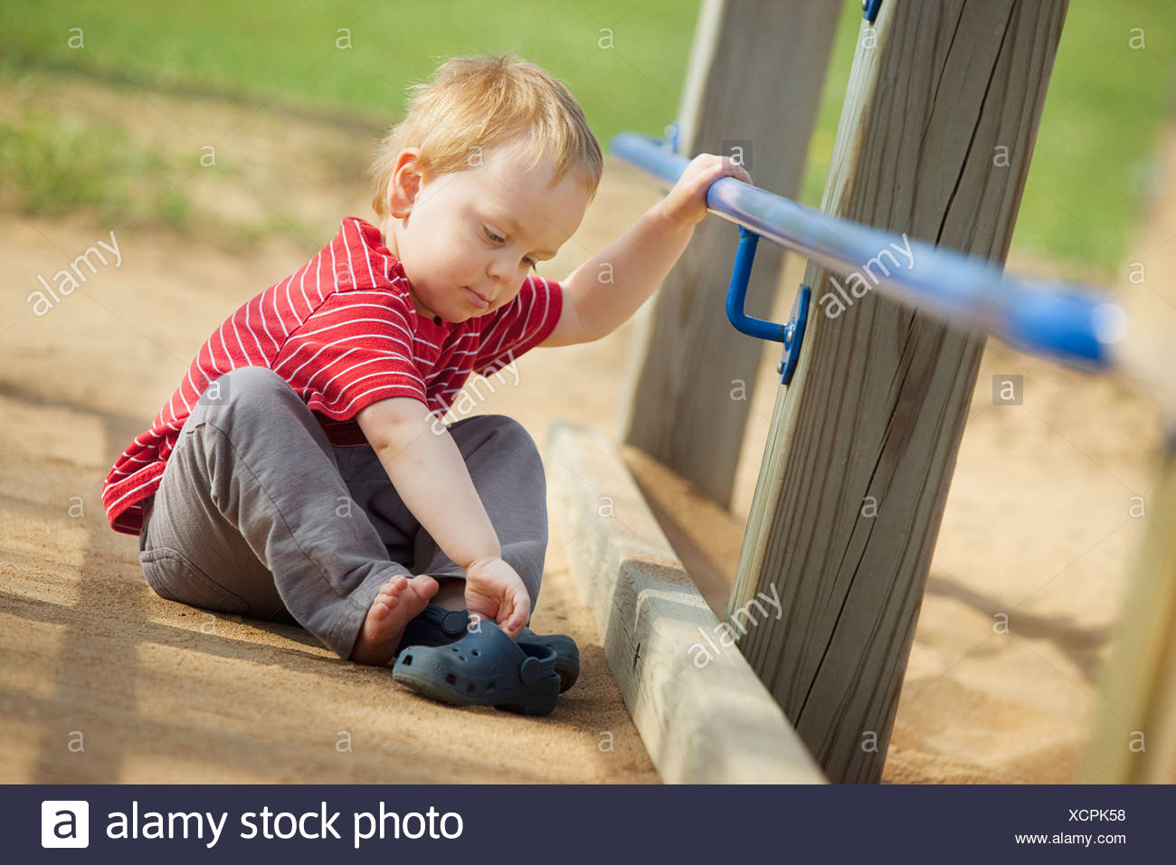 Young Boy Taking Off His Shoes At The Park - Stock Image