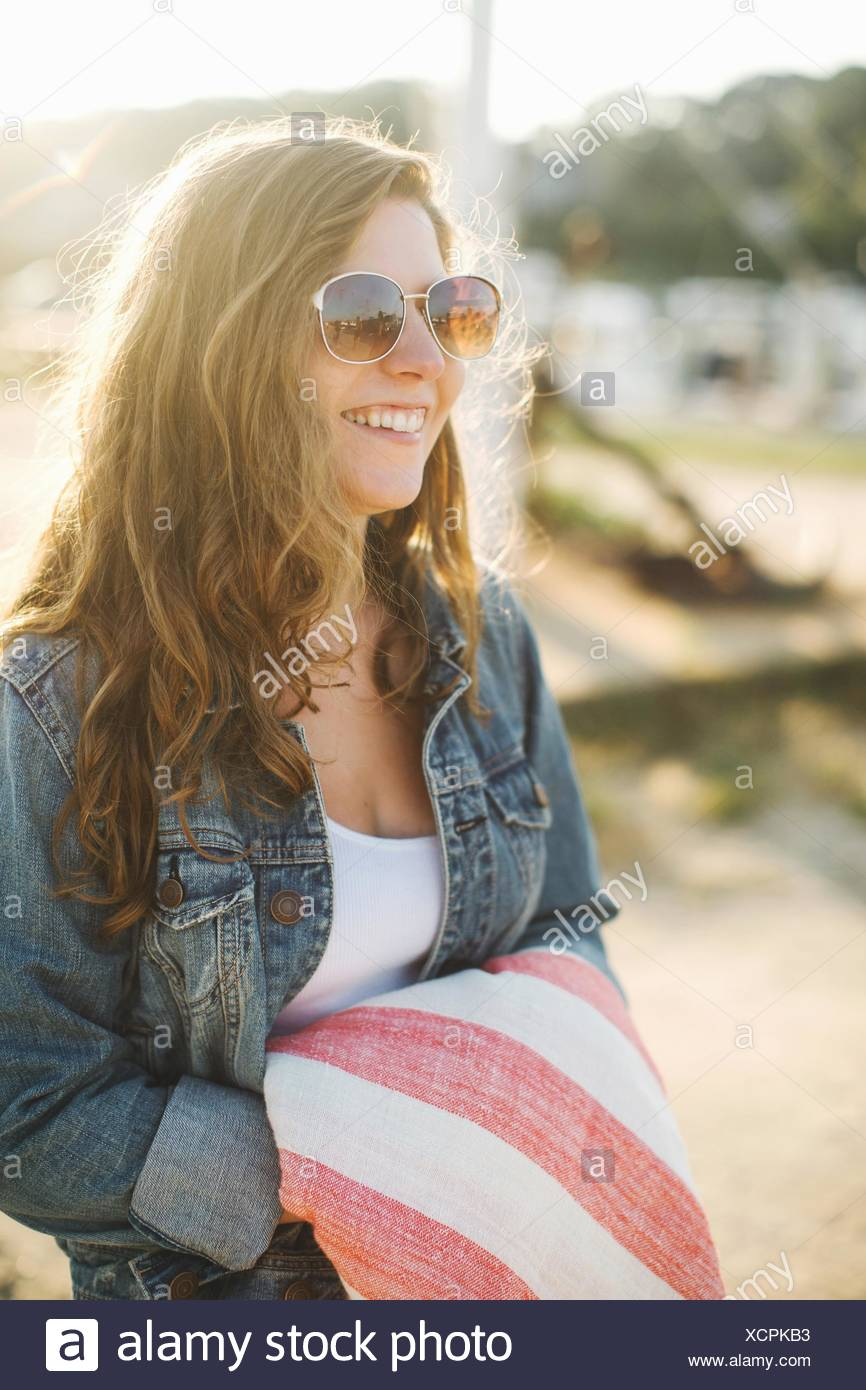 e5377a6ba6 Women wearing denim jacket and sunglasses holding blanket looking away  smiling