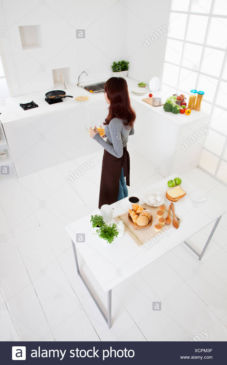 Young woman standing in the kitchen, - Stock Image