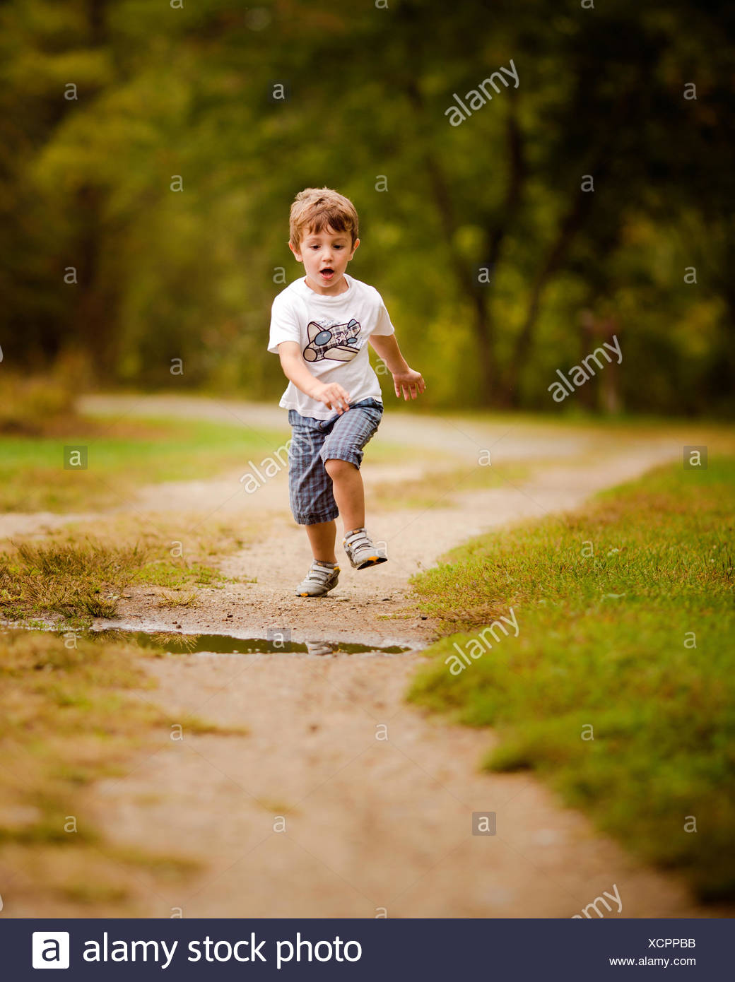 Boy running along footpath about to jump over a puddle - Stock Image