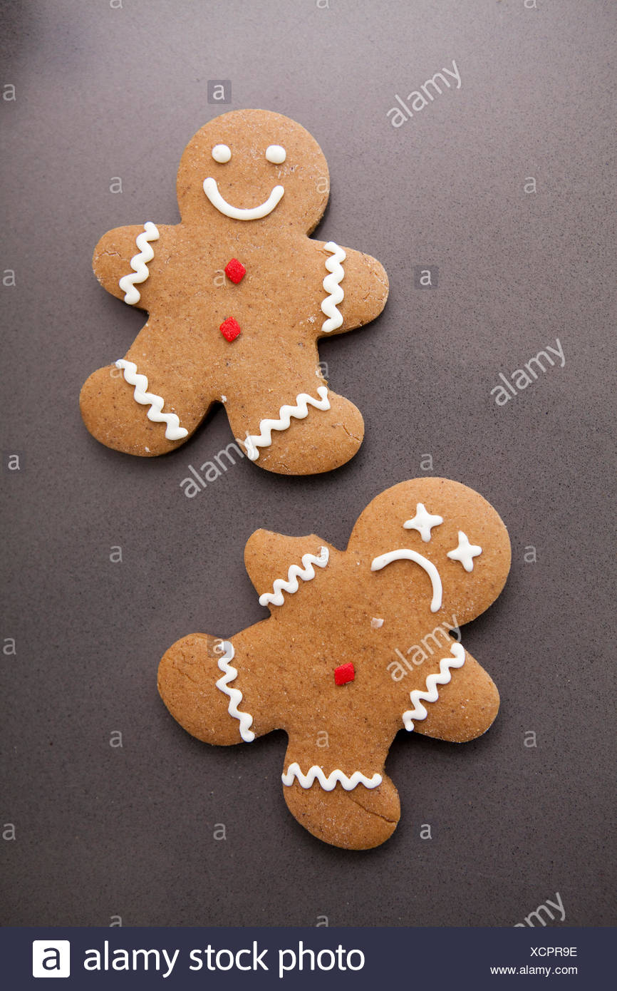 Two gingerbread men on grey background - Stock Image