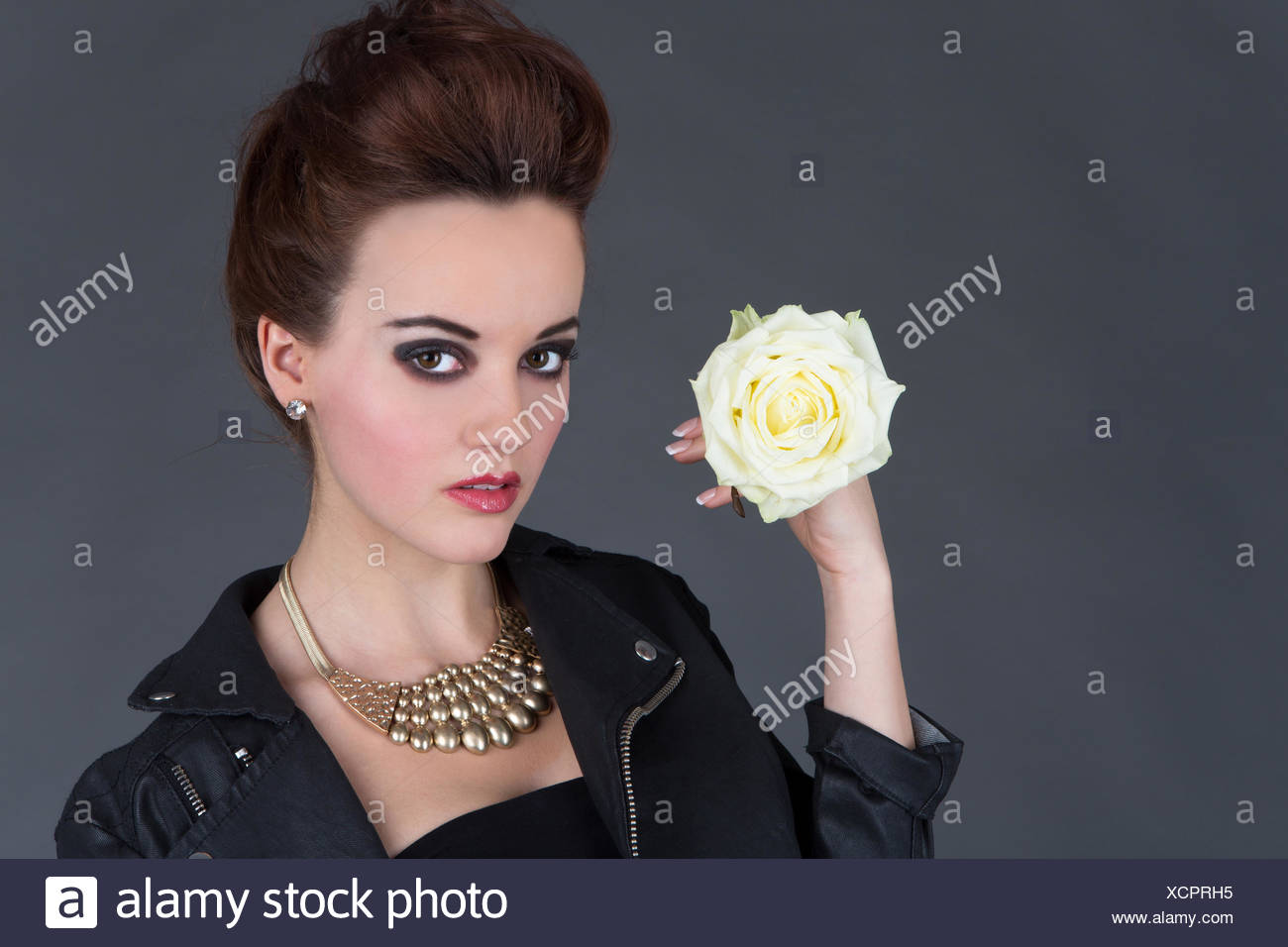 Young woman in leather outfit with white rose - Stock Image