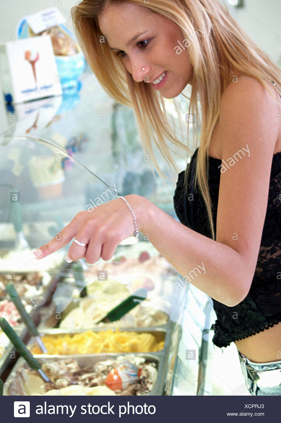 blond young woman in an ice cream parlor chosing the sorts with a smile Stock Photo