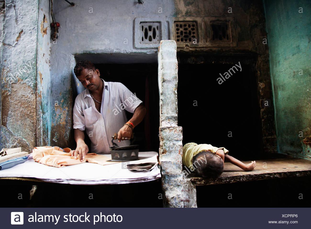 Man ironing clothes while his child naps, Varanasi, India - Stock Image