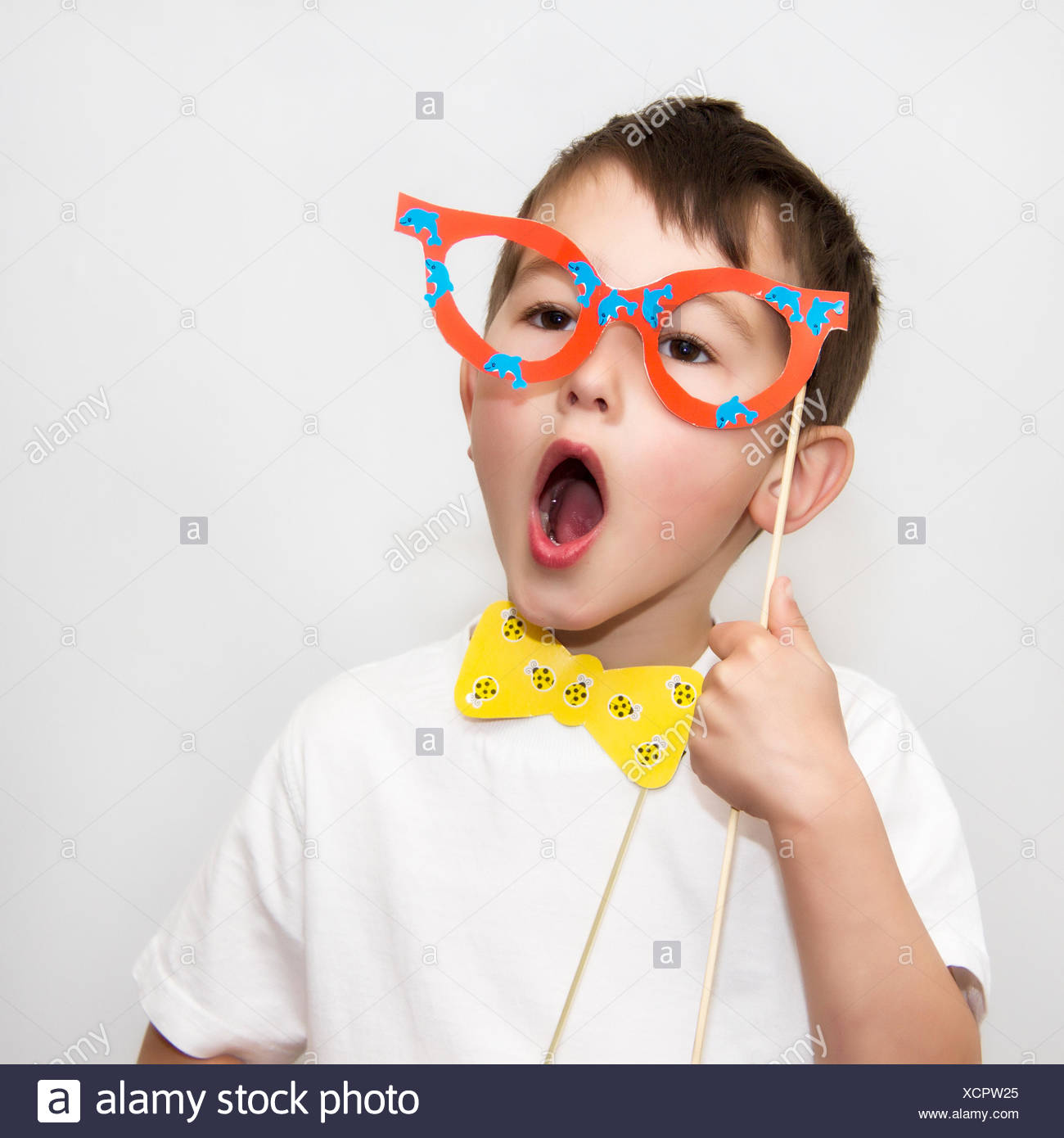 Boy with glasses and bow-tie masks - Stock Image