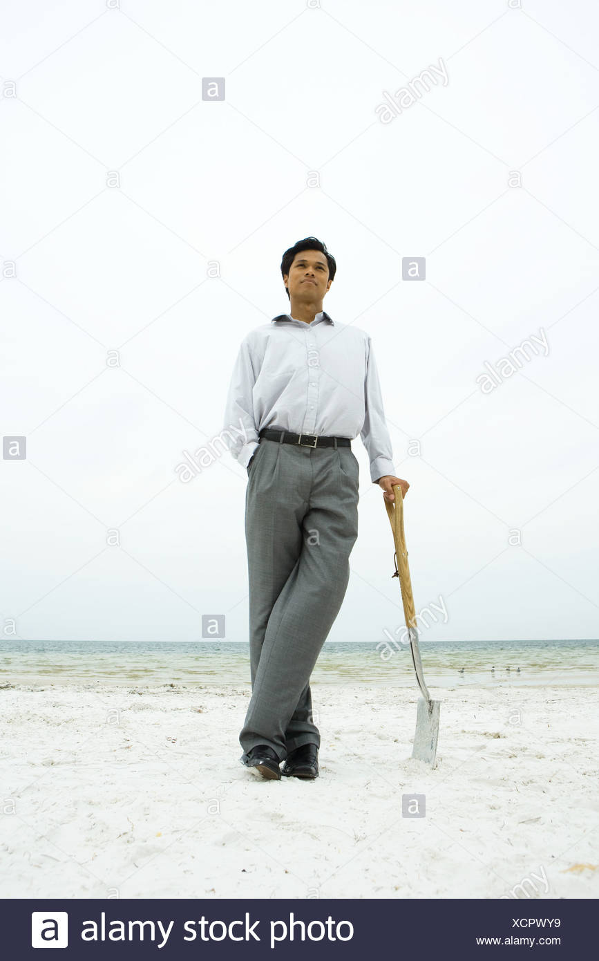 Man standing at the beach, leaning against shovel, hand in pocket - Stock Image