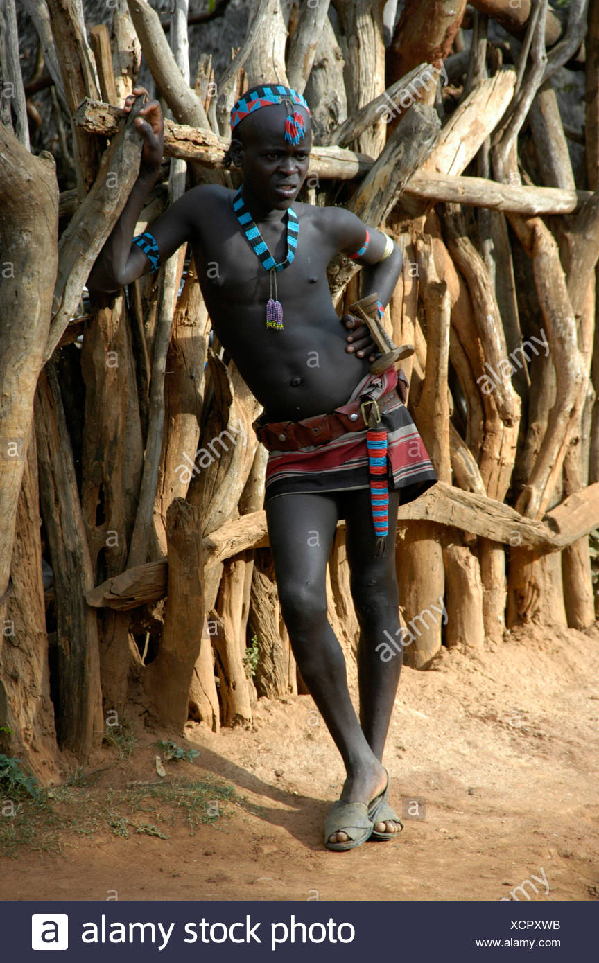 Young man wearing a mini skirt and a colourful necklace, leaning against a wooden fence, Keyafer, Ethiopia, Africa - Stock Image