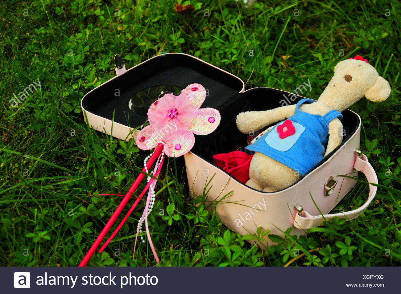 Suitcase with teddy bear and wand Stock Photo