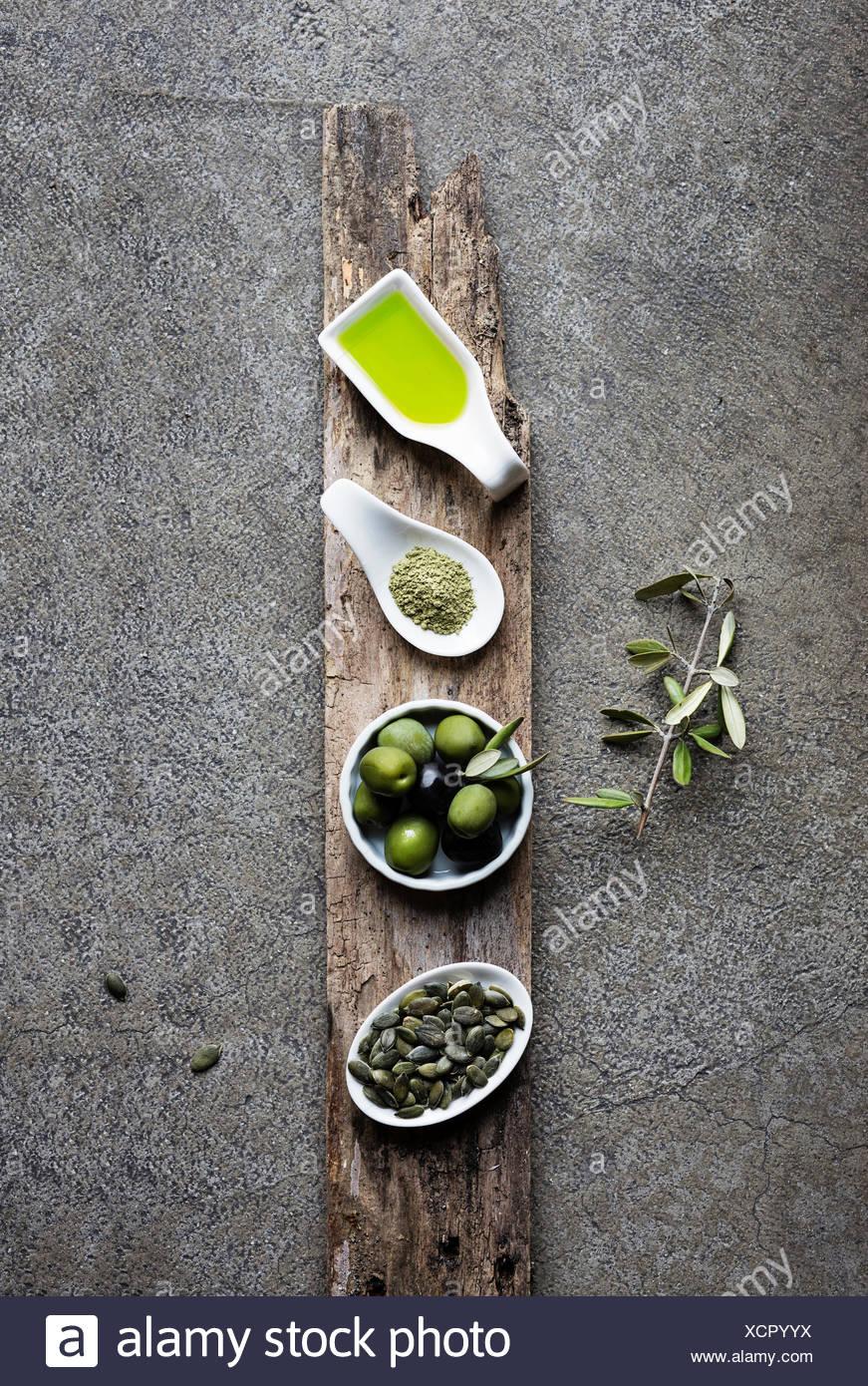 Green food: olive oil, macha tea, olives, pumpkin seed on grey background Stock Photo