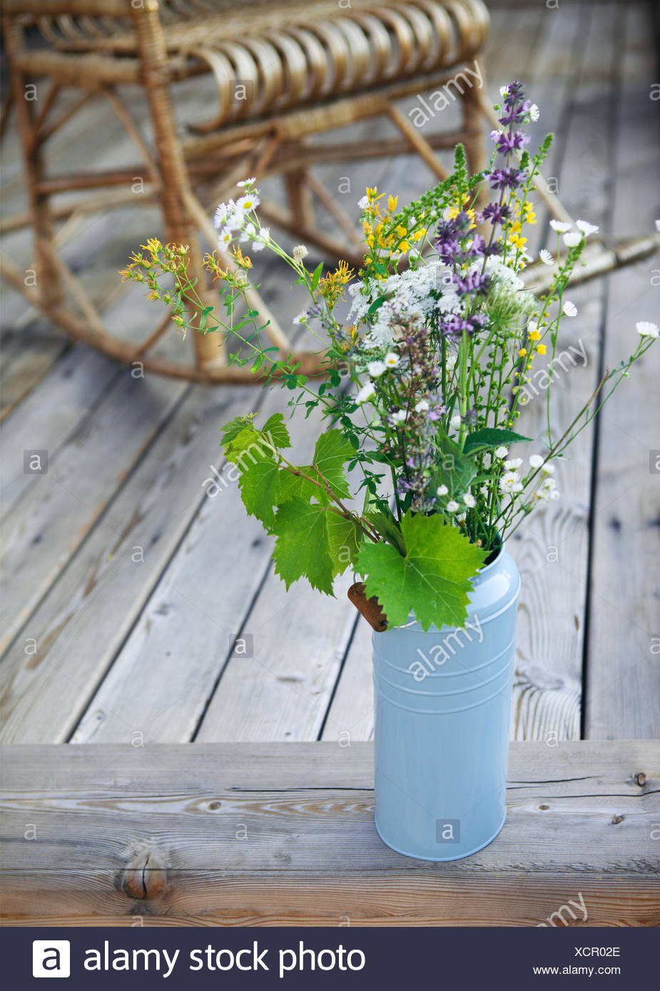 Bright yellow and blue flowers on porch - Stock Image