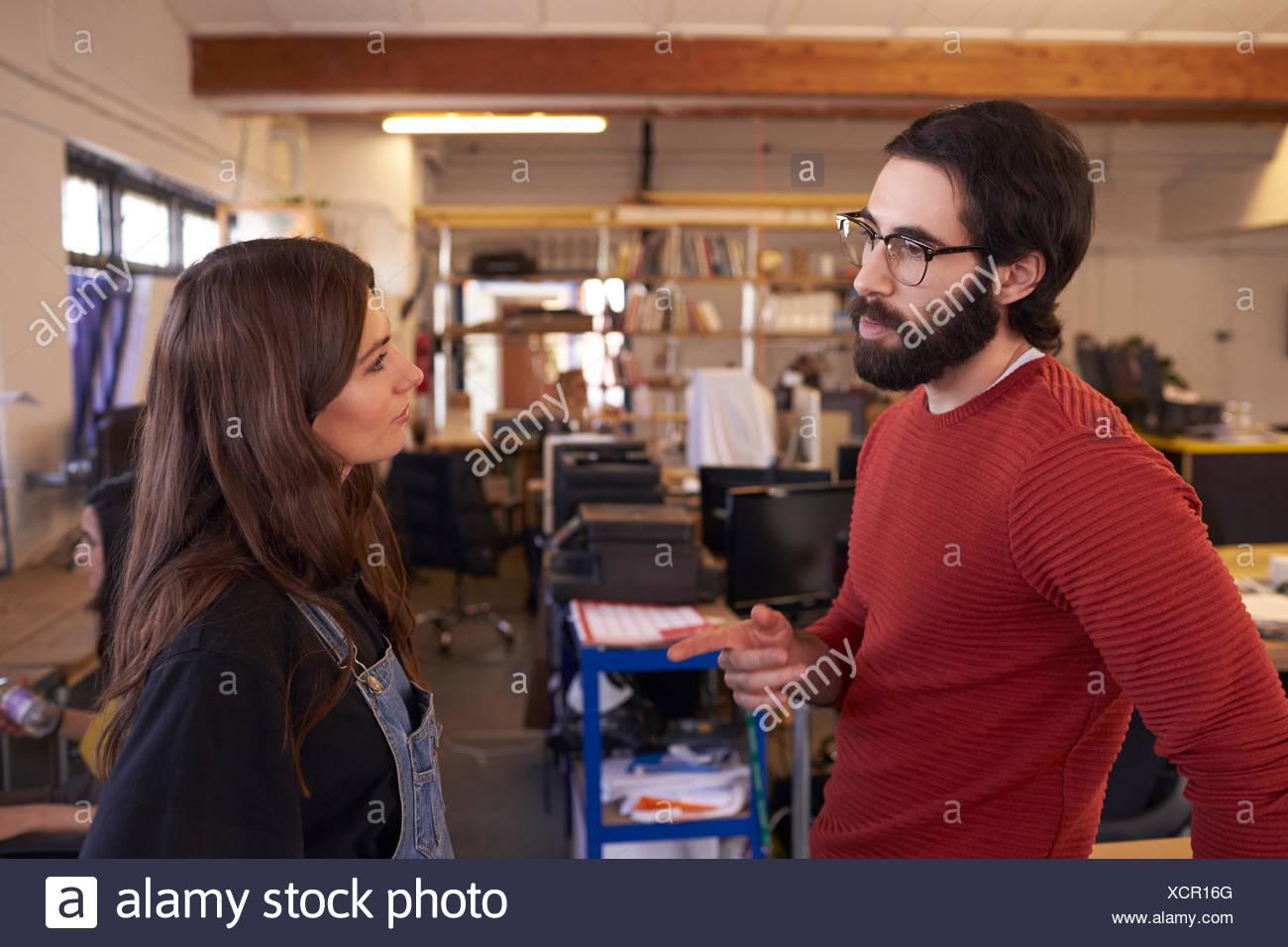 Two Designers Having Informal Meeting In Modern Office - Stock Image