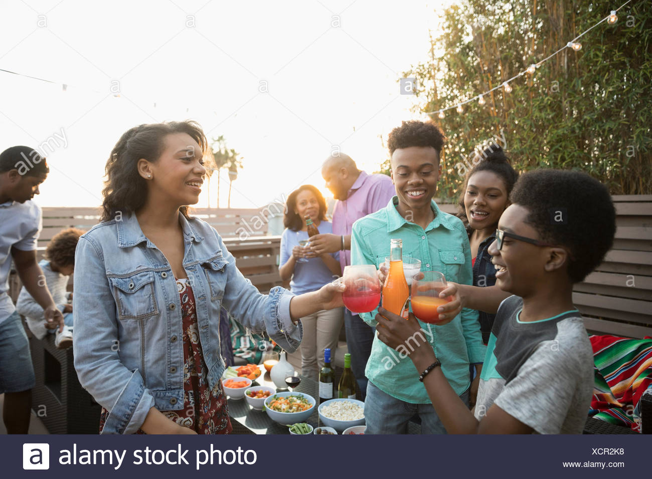 African American family toasting soda glasses, enjoying barbecue on summer deck - Stock Image
