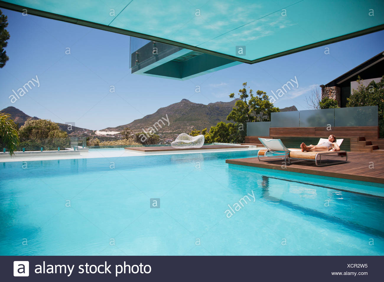Awesome Woman Sunbathing On Lounge Chair At Poolside With Mountain Ncnpc Chair Design For Home Ncnpcorg