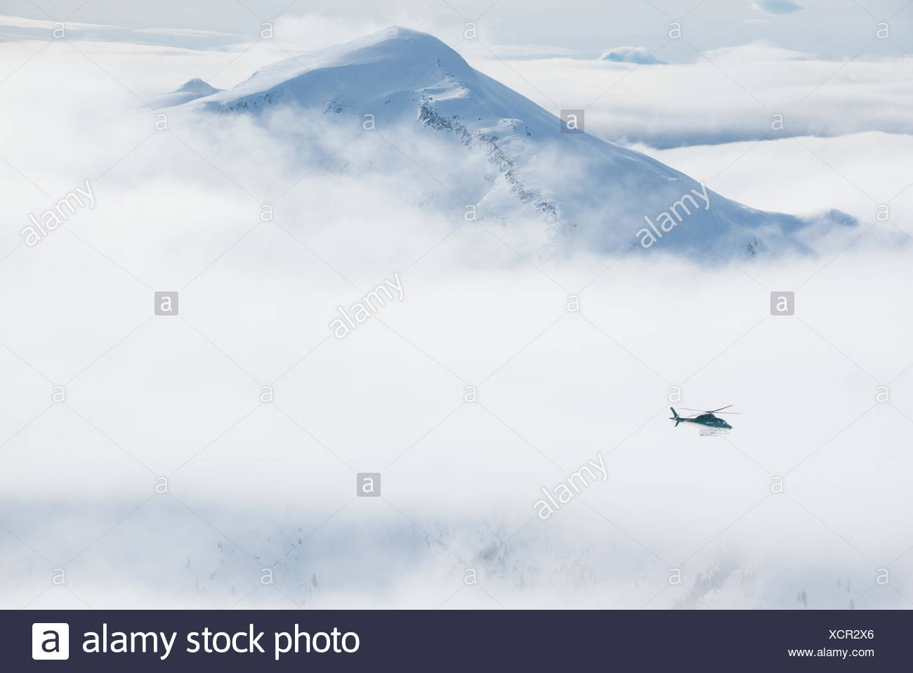 An A-Star helicopter flies past a remote mountain peak Northern Escapes heli-skiing near Terrace, British Columbia - Stock Image