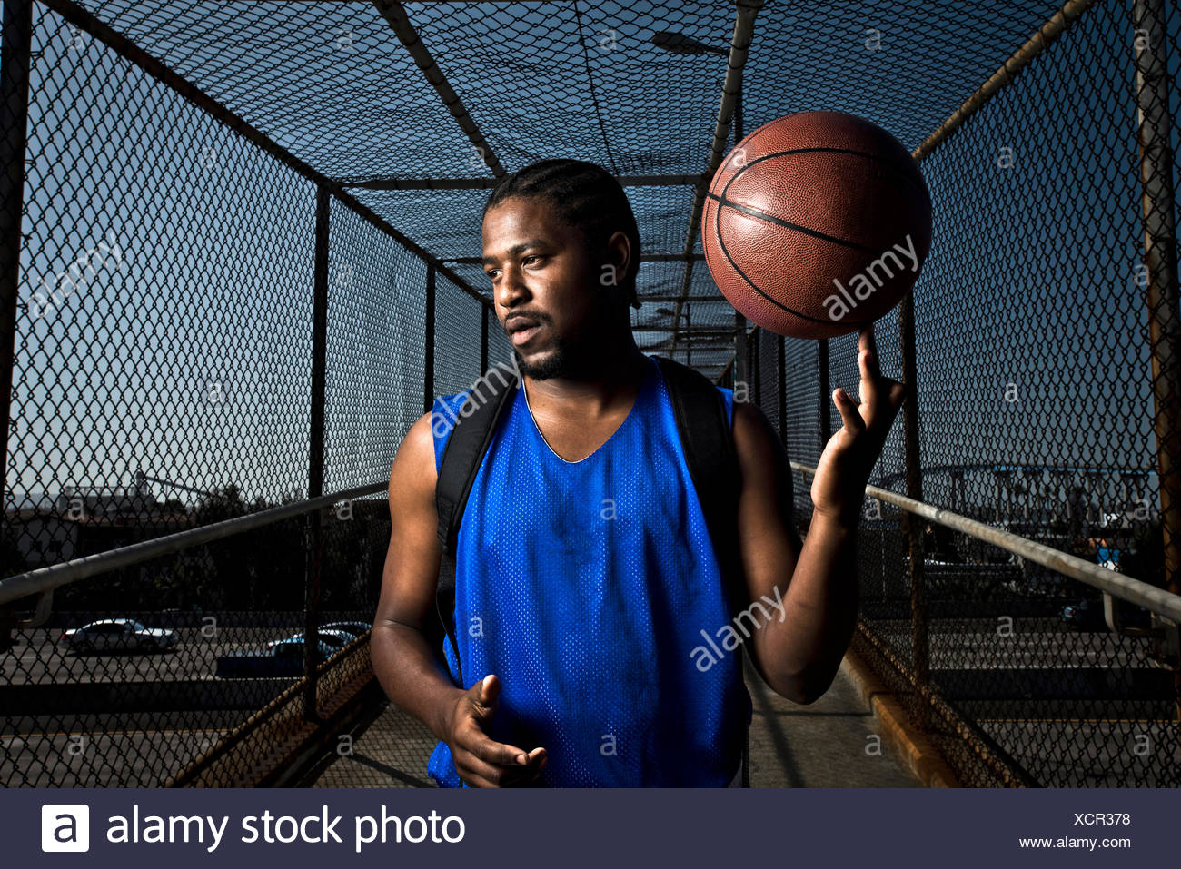 An athletic male spins a basketball on his finger. - Stock Image