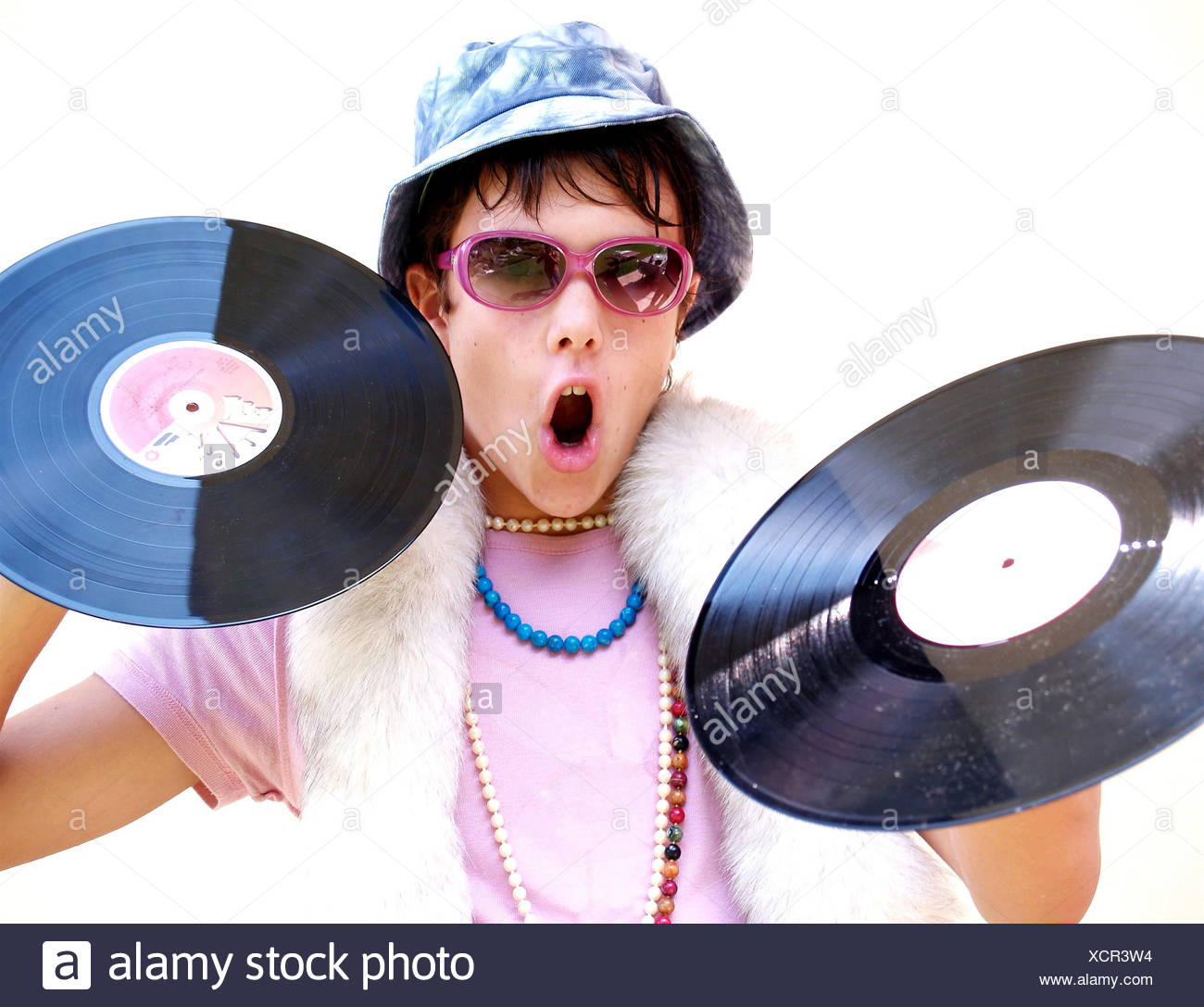young disc jockey in a freaky outfit holding up vinyl discs - Stock Image