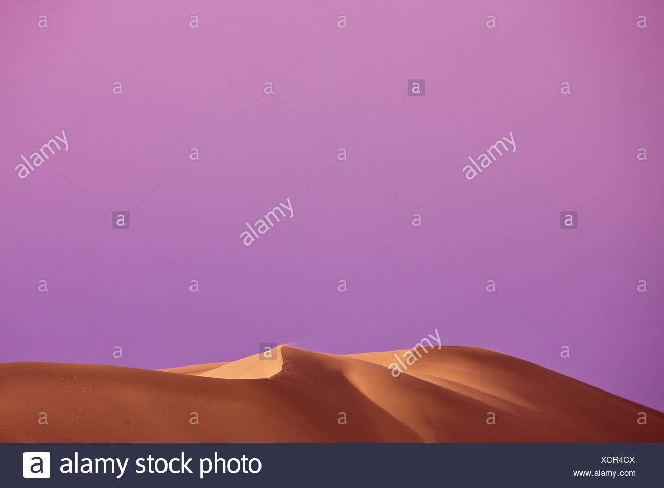 500-foot windswept dunes rise above the Amargosa River. - Stock Image