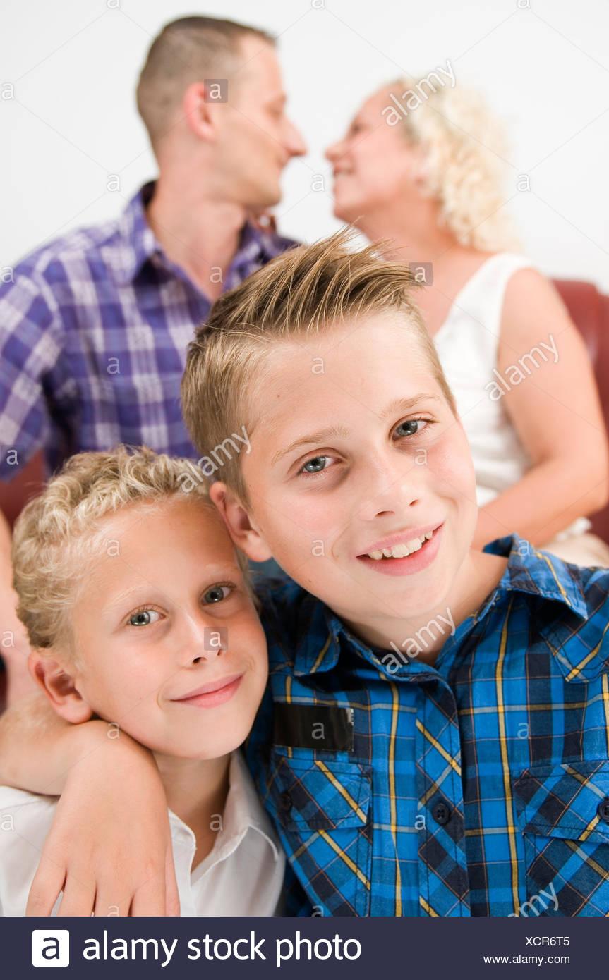 Kopf-und-Schulter-Porträts zweier Brüder im Alter von 7 und 13 Jahren mit ihren unscharf abgebildeten Eltern im Hintergrund auf einem Sofa sitzend und sich gegenseitig anschauend - Stock Image
