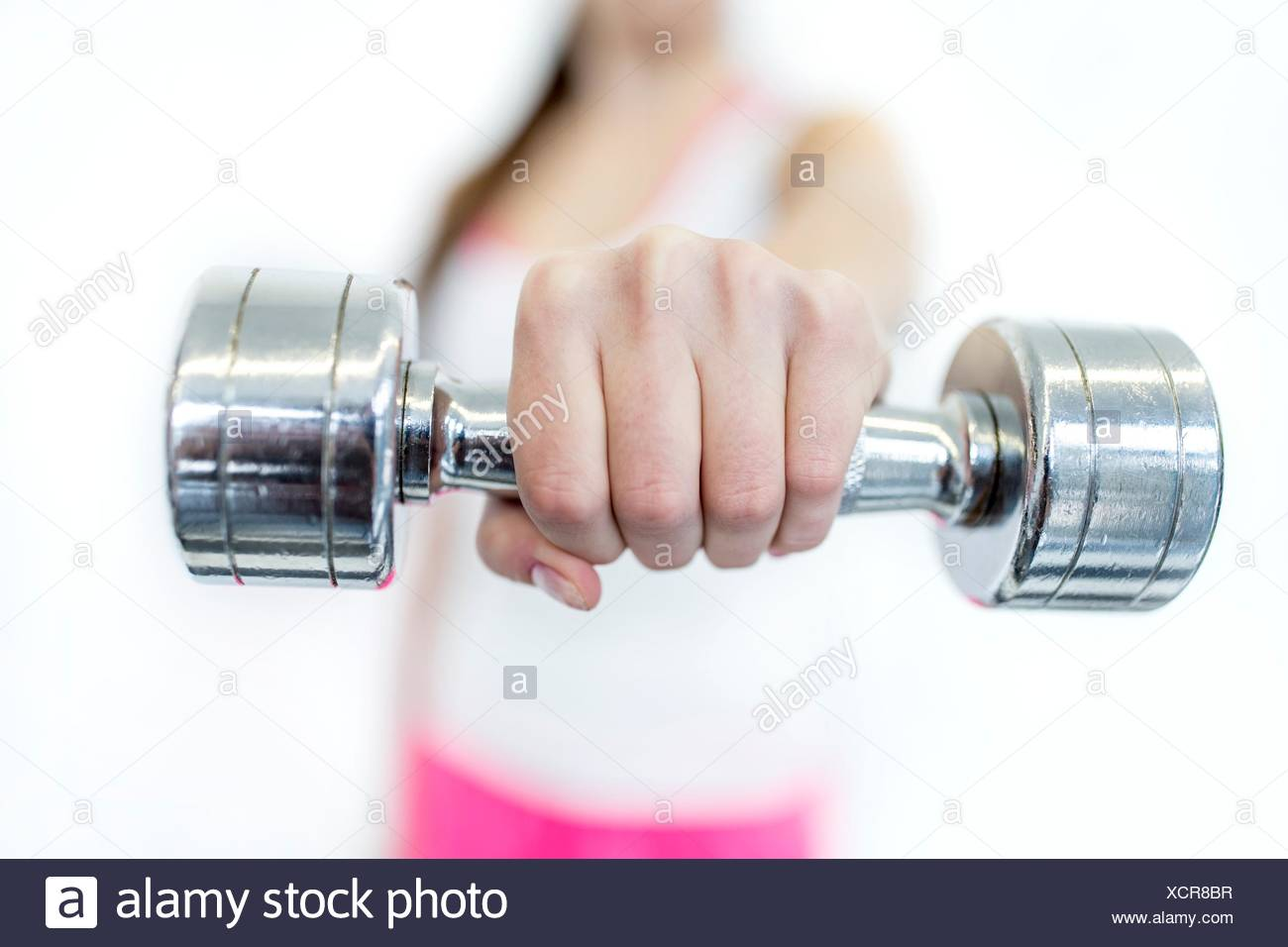PROPERTY RELEASED. MODEL RELEASED. Young woman working out with dumbbell, close-up. - Stock Image