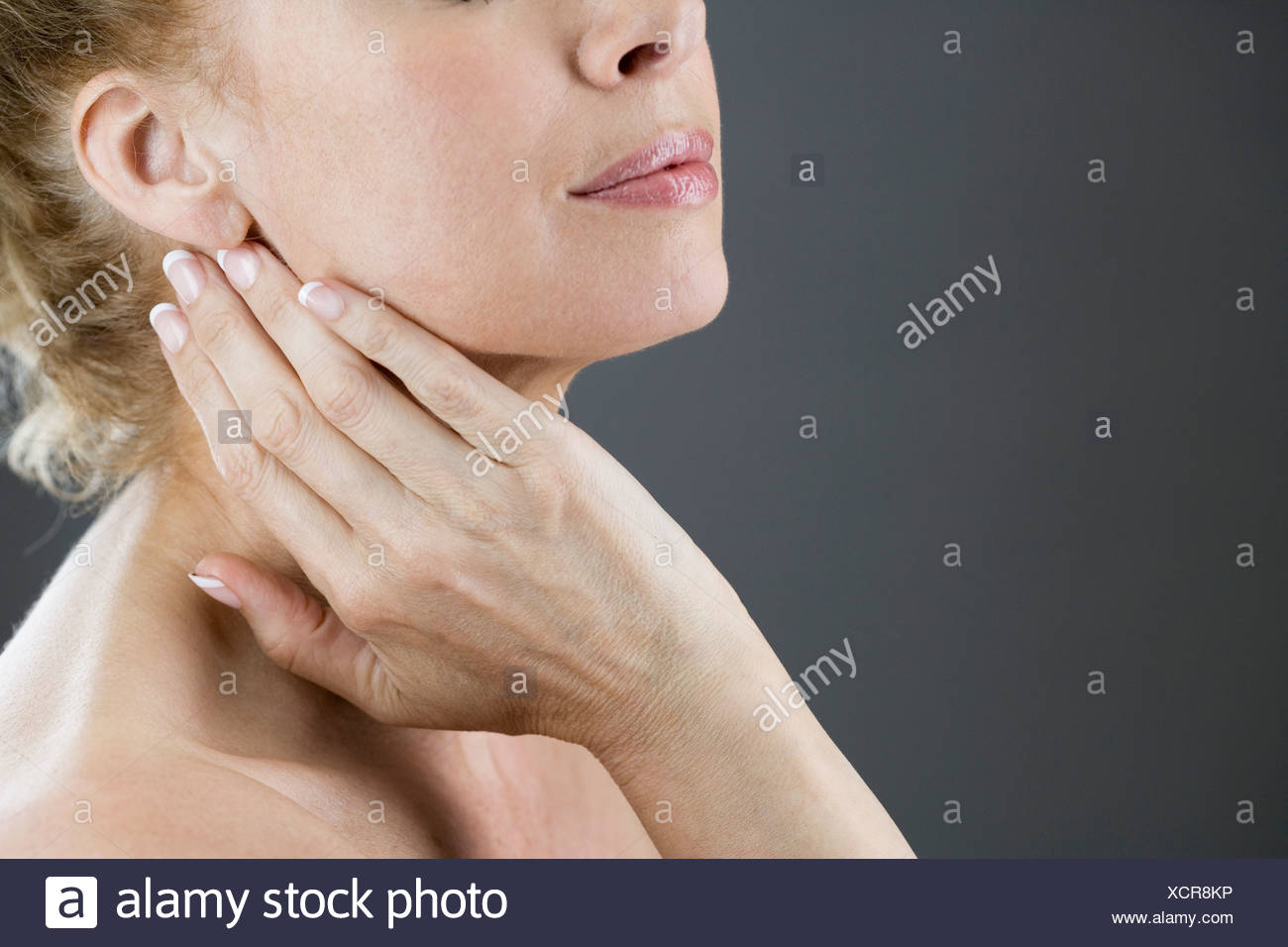 A woman touching her neck - Stock Image