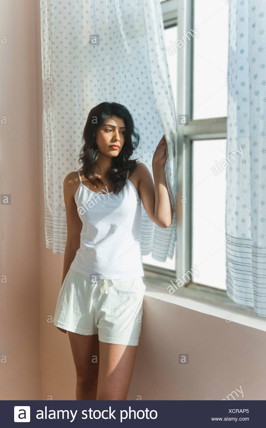 Woman looking through a window - Stock Image