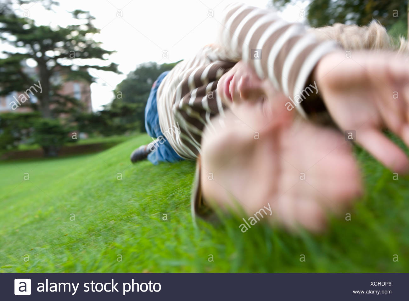 Boy (10-12) rolling down hill - Stock Image
