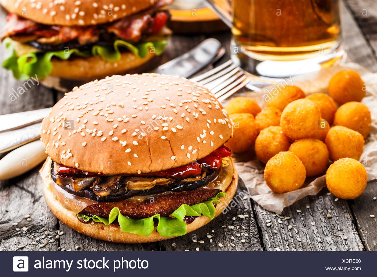 Delicious burgers with fried potato balls and beer on a rustic table - Stock Image