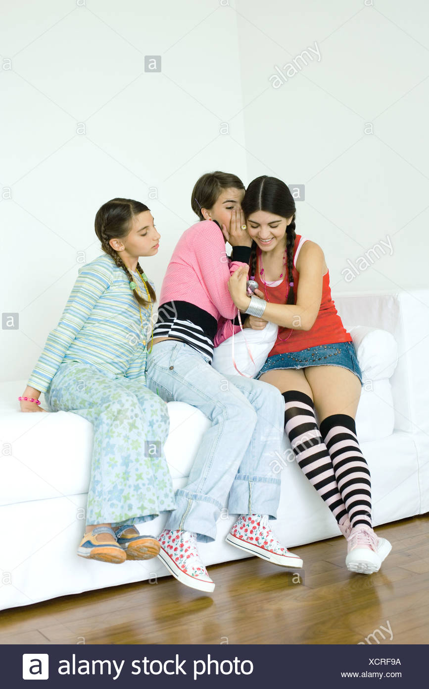 Three young female friends sitting on sofa, one whispering to the other while third eavesdrops - Stock Image