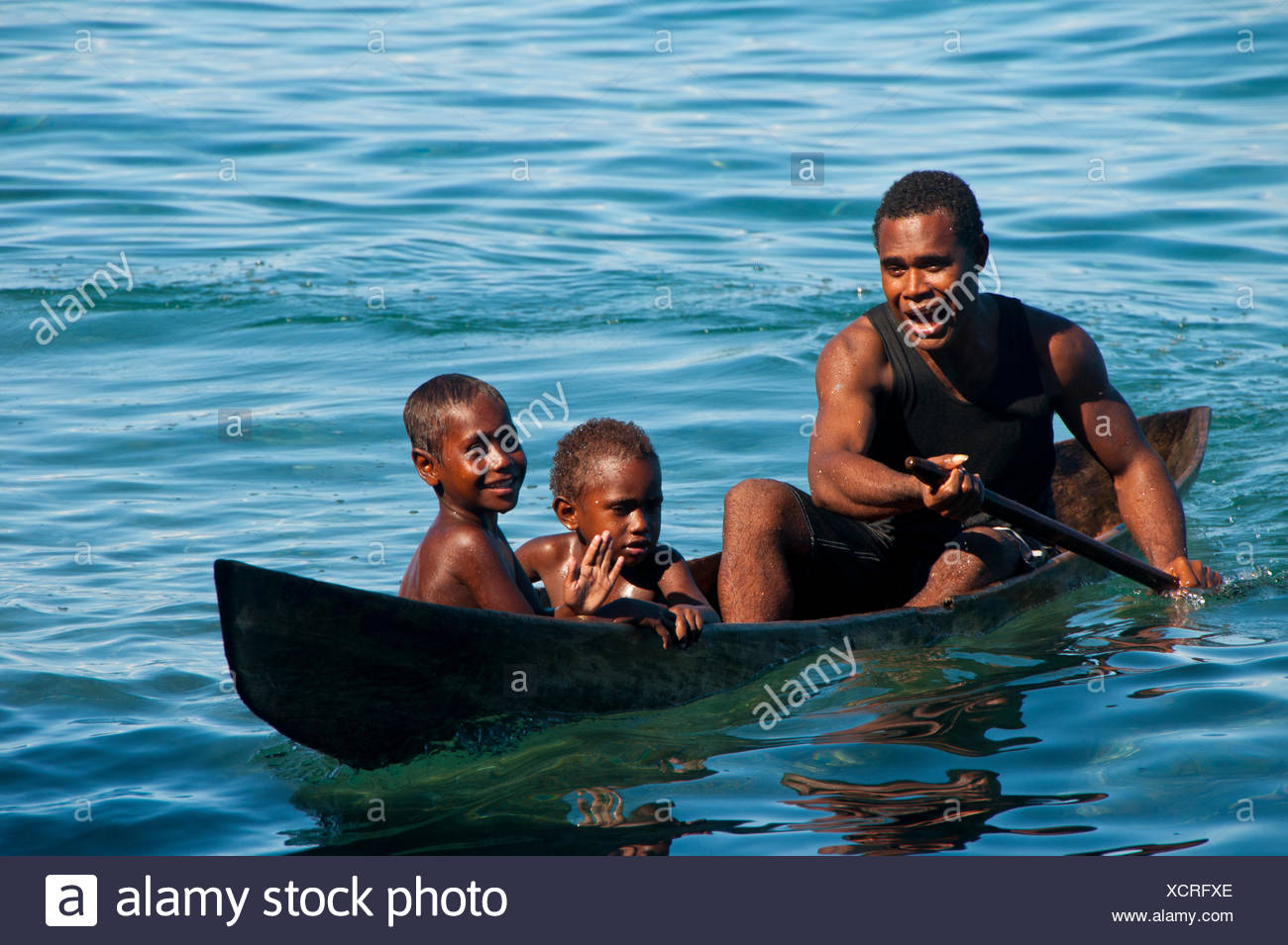 A man and two children in a canoe, Savo Island, Central Province, Solomon Islands - Stock Image