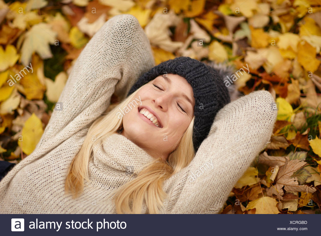 Woman laying in autumn leaves outdoors Stock Photo
