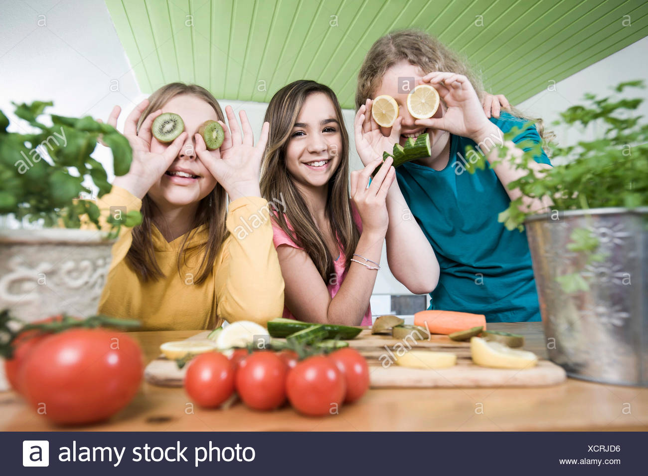 Girls in kitchen making faces with fruit - Stock Image