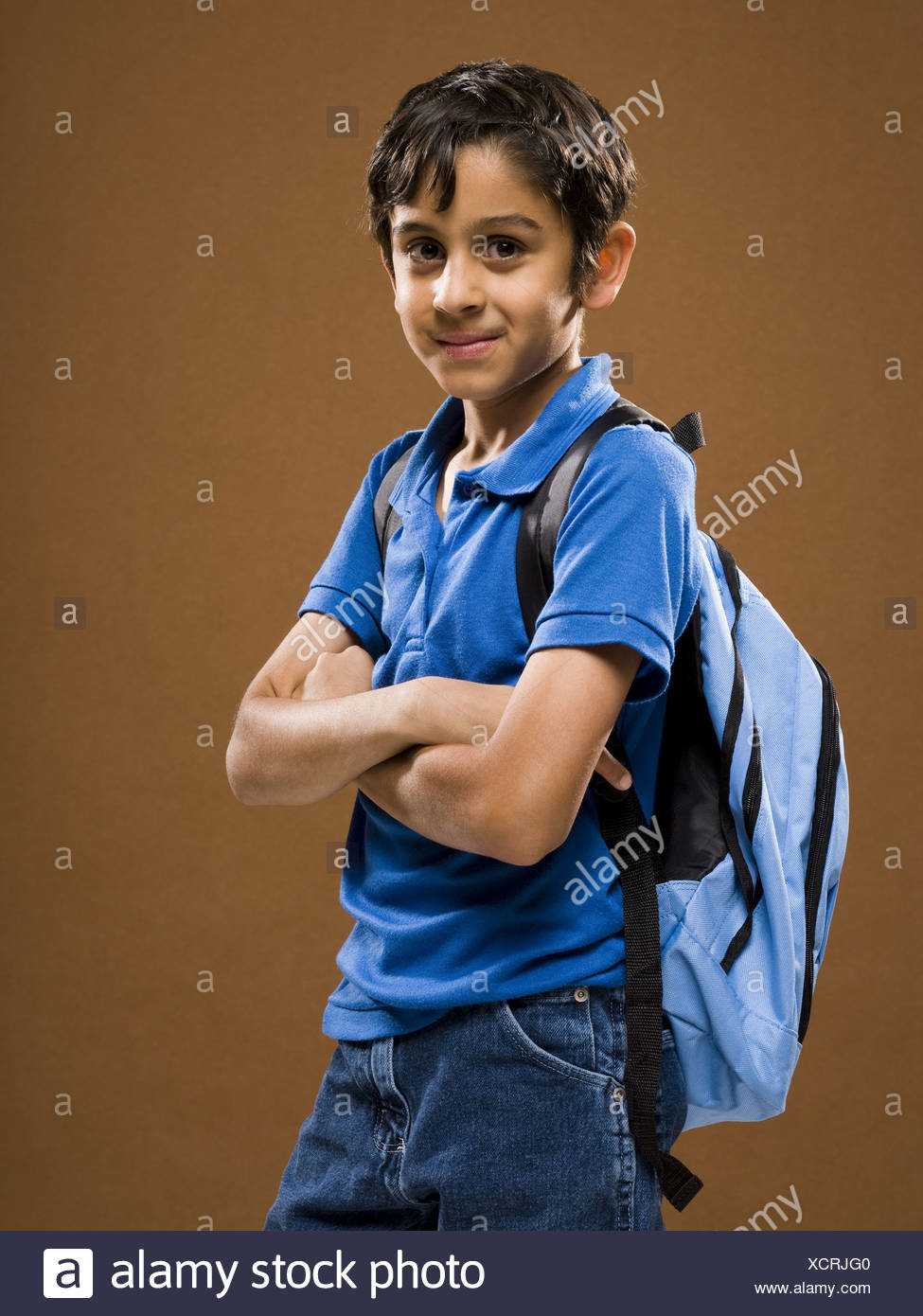 Boy standing with arms crossed and backpack smiling - Stock Image
