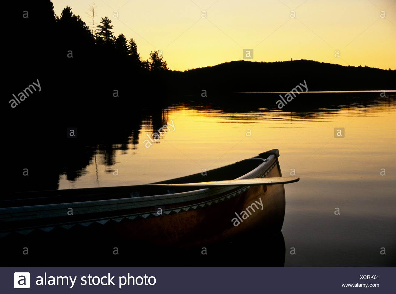The sillhouette of a canoe as it rests on the shore of a lake at sunset on Booth Lake in Alqonguin Provincial Park, Ontario, Can - Stock Image