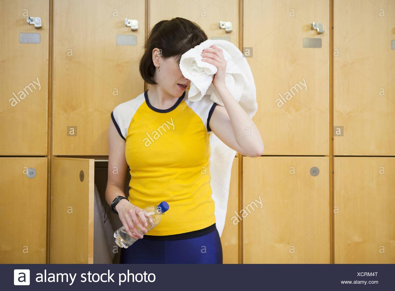 Woman wiping sweat in locker room Stock Photo