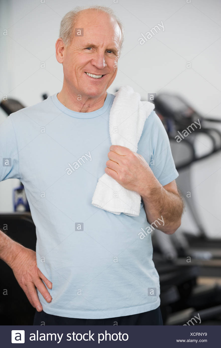 Senior man in front of exercise machines - Stock Image