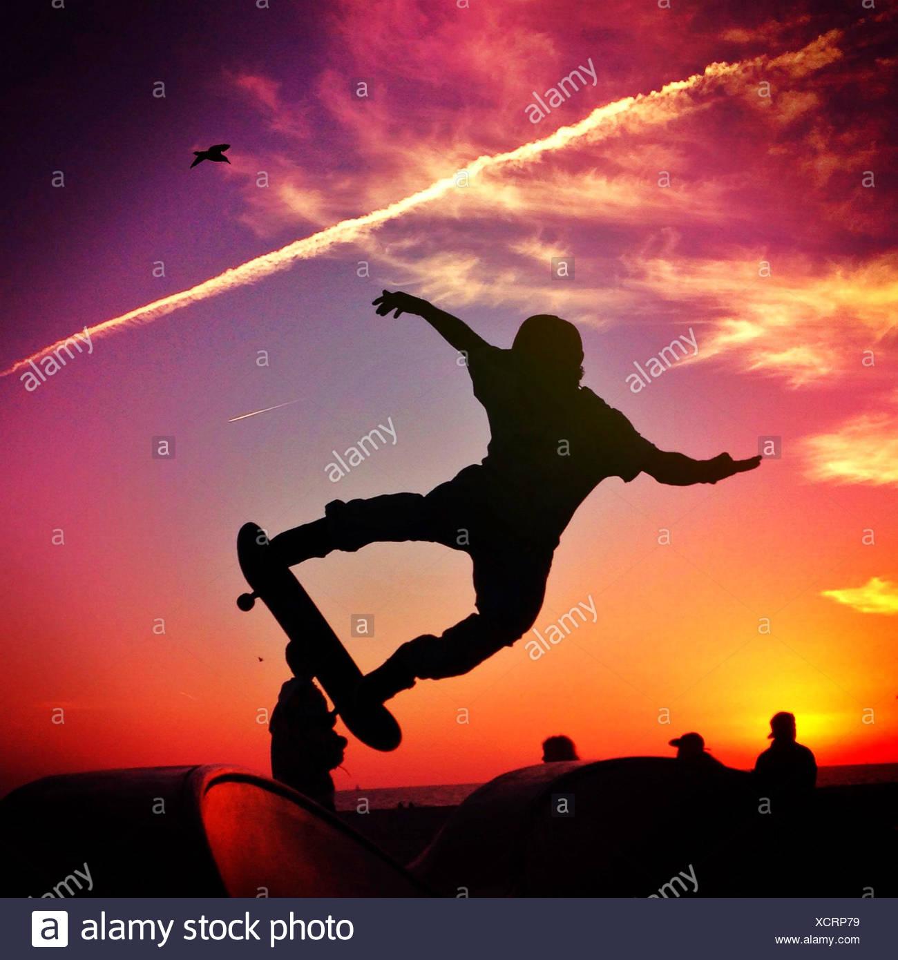 Silhouette of man Skateboarding at sunset - Stock Image