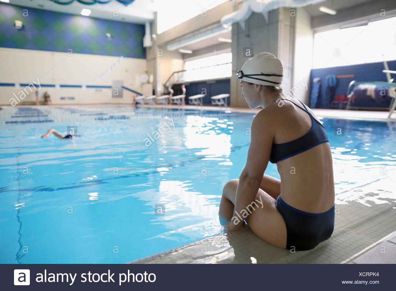 Mother swimmer watching daughter swimming in swimming pool - Stock Image