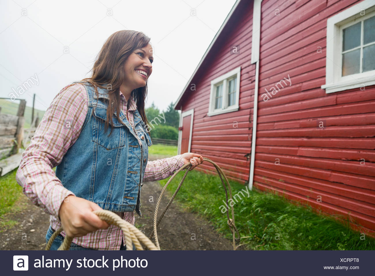 Smiling woman holding lasso outside barn - Stock Image