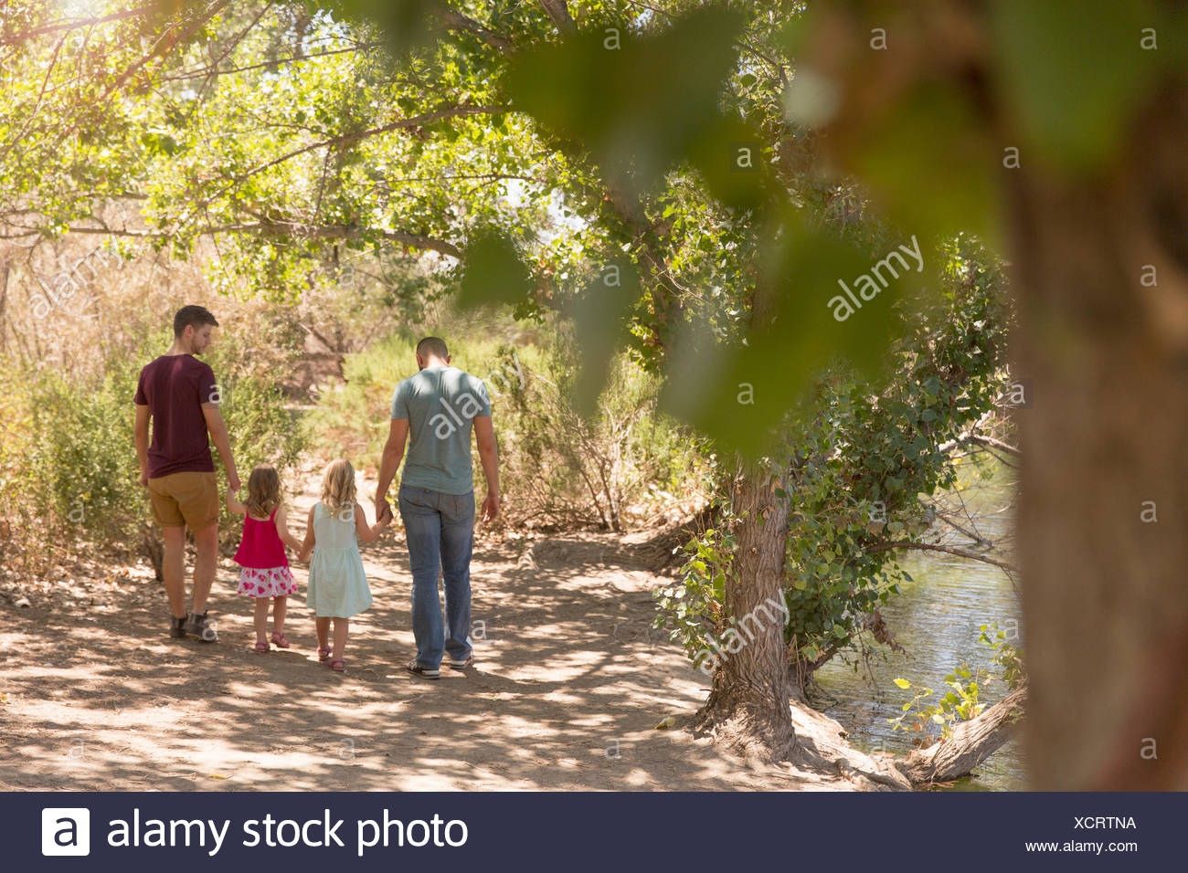 Rear view of male couple strolling with two daughters in park Stock Photo